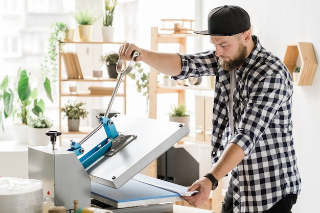 Young contemporary craftsman using special equipment while printing decor on workpiece of pet collar