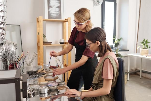 マスタークラス中に長いガラスのワークピースを燃やす方法を研修生に示す作業服と眼鏡の若い現代の職人