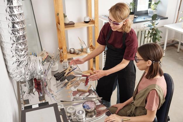 ガラスのワークピースを処理するためにバーナーを使用する方法を研修生に示す作業服と眼鏡の若い現代の職人