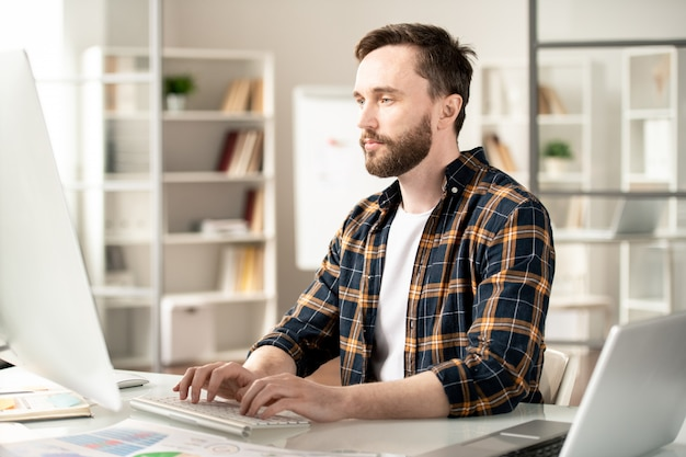 Young contemporary designer or programmer looking attentively at computer screen while working over new website