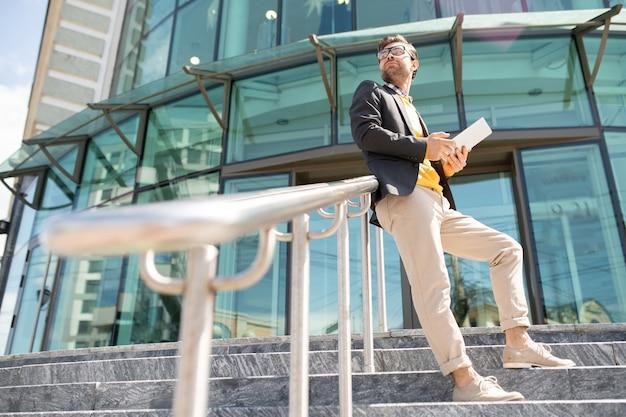 비즈니스 센터와 계단에 난간에 의해 서 터치 패드와 젊은 현대 우아한 사업가