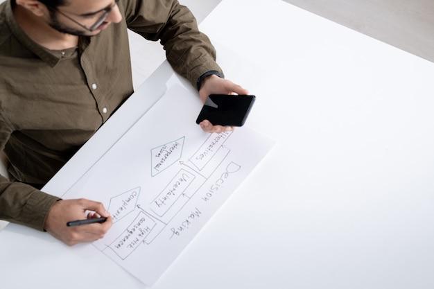 젊은 현대 엔지니어 또는 회계사 펜 및 스마트 폰 책상에 앉아있는 동안 종이에 흐름도를 그리기