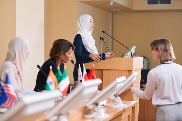 ヒジャーブとスーツで政治会議でトリビューンのそばに立っている間マイクで話す若い現代女性代表
