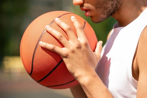 Молодой современный баскетболист, держащий мяч за лицо и грудь, готовясь к передаче