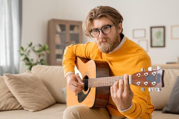 Молодой современный музыкант в повседневной одежде играет на акустической гитаре во время онлайн-курса создания музыки дома