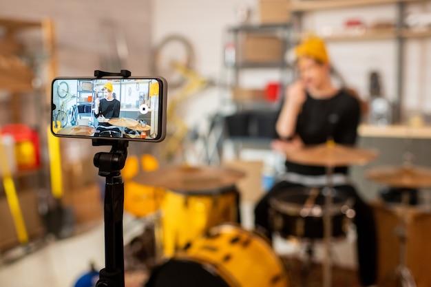 그의 온라인 구독자를 위해 드럼 음악에 대한 비디오를 만드는 동안 스마트 폰 화면에 drumset 앞에 젊은 현대 남자