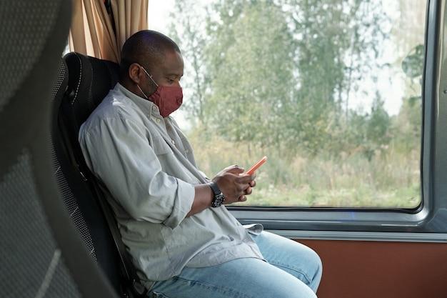 Молодой современный человек в защитной маске прокручивает мобильный телефон