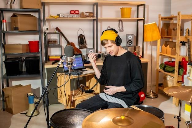 드럼 키트와 노트북 앞에 앉아 셰이커를 사용하여 새로운 음악을 만들고 차고에서 녹음하는 젊은 현대 음악가