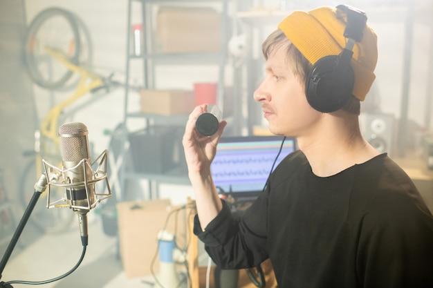 마이크 앞에 앉아 차고에서 새로운 음악을 녹음하는 동안 셰이커를 사용하는 헤드폰을 가진 젊은 현대 음악가