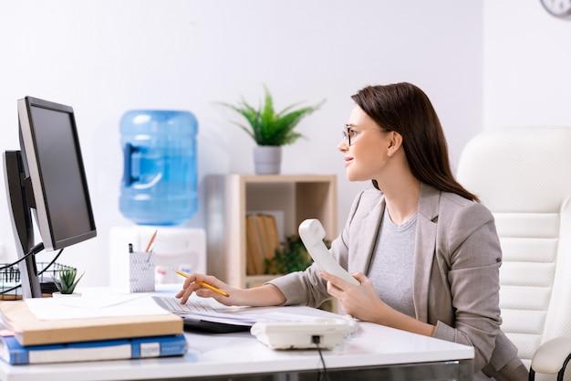 コンピューターの画面の前に机のそばに座って、受話器を持っている若い現代のオフィスマネージャーまたは事業会社の責任者