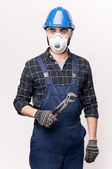 作業服、ヘルメット、手袋、保護マスクを身に着けた若い現代の配管工または修理工が、孤立して立っているときに手工具を保持している