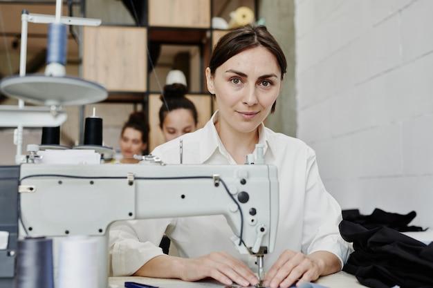 Молодая современная швея смотрит на вас, сидя на рабочем месте с электрической швейной машиной и шьет или ремонтирует одежду