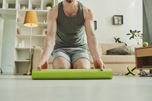 Young contemporary sportsman standing on his knees while unrolling green mat for exercising on the floor in home environment