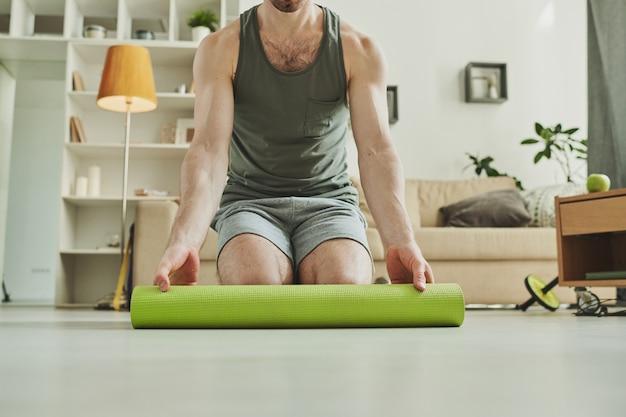 Молодой современный спортсмен, стоящий на коленях, разворачивает зеленый коврик для занятий на полу в домашних условиях
