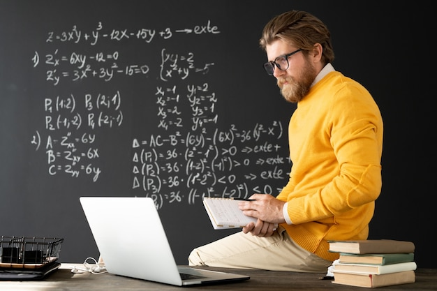 Young contemporary teacher with copybook sitting on table in front of laptop and talking to his online audience about algebraic formulas