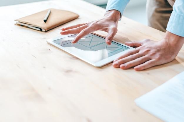 새로운 인터페이스를 통해 작업하는 동안 터치 패드 화면에서 애플리케이션 디자인을 가리키는 젊은 현대 웹 디자이너