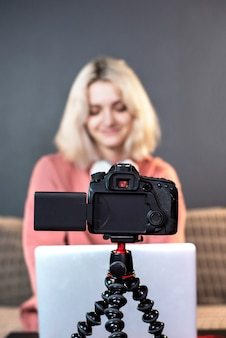 Young content creator blonde girl is on her laptop on the table