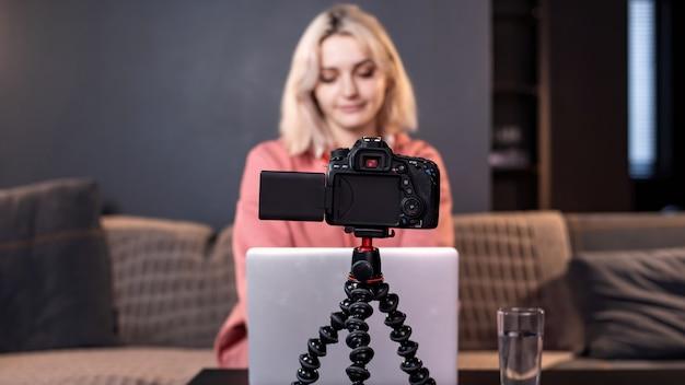 젊은 콘텐츠 제작자 금발 소녀는 테이블에 그녀의 노트북에 있습니다. 삼각대에 카메라를 사용하여 자신을 촬영합니다. 재택 근무. 동영상 블로그 녹화
