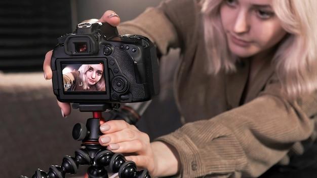 젊은 콘텐츠 제작자 금발 소녀가 삼각대에 카메라를 장착하고 동영상 블로그에 대해 이야기하는 자신을 촬영합니다.