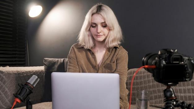 삼각대에 카메라와 함께 테이블에 그녀의 노트북에서 일하는 헤드폰으로 젊은 콘텐츠 제작자 금발 소녀