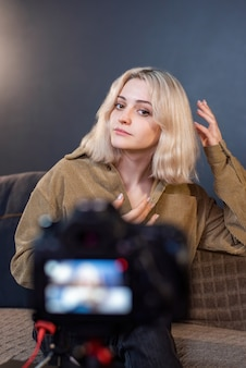 삼각대에 카메라를 사용하여 자신을 촬영하는 젊은 콘텐츠 제작자 금발 웃는 소녀. 재택 근무. 동영상 블로그 녹화