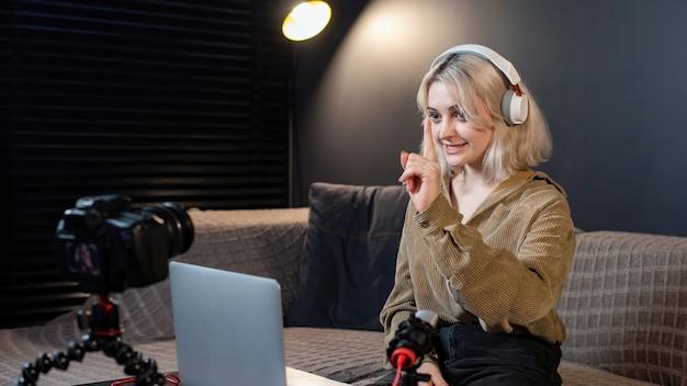 테이블에 그녀의 노트북과 젊은 콘텐츠 제작자 금발 웃는 소녀. 삼각대에 카메라를 사용하여 자신을 촬영합니다. 재택 근무. 동영상 블로그 녹화