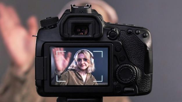Giovane bionda creatore di contenuti parlando e gesticolando ragazza si riprende utilizzando una fotocamera su un treppiede