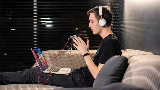 L'uomo giovane creatore di contenuti è sul suo laptop seduto sul divano alla conferenza. mani unite. lavorare da casa