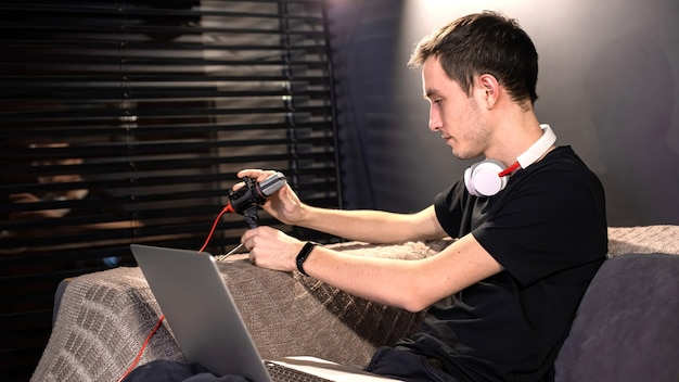 Young content creator man is setting up the microphone, laptop on his knees, sitting on the sofa. working from home