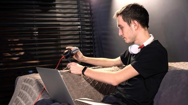若いコンテンツクリエーターの男性が、ソファに座ってマイクとラップトップを膝の上に置いています。家で働く