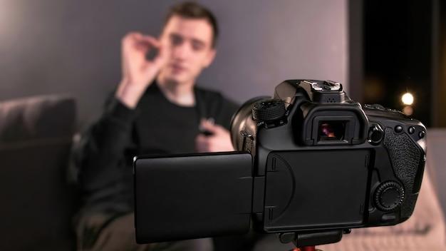 Giovane creatore di contenuti parlando e gesticolando uomo che si riprende utilizzando una fotocamera su un treppiede