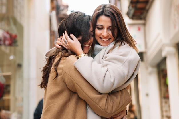 Молодой контент женщин, обнимающихся в любви