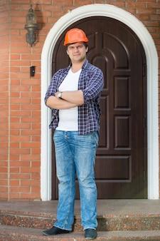 Молодой подрядчик позирует на каменной лестнице перед новым домом