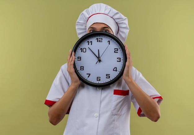 孤立した緑の壁に壁時計でシェフの制服で覆われた顔を身に着けている若い料理人の女性