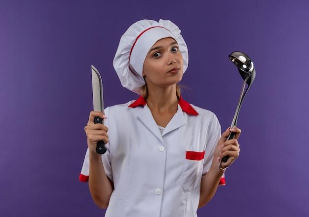 Молодая женщина-повар в униформе шеф-повара держит ковш и нож на изолированной стене