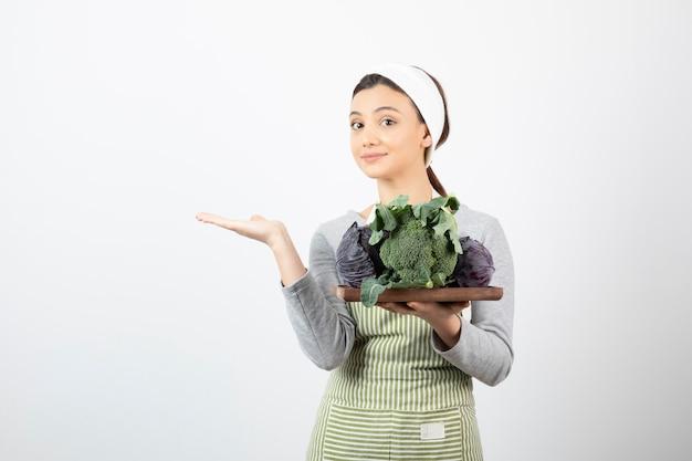 Giovane cuoco che tiene piatto di cavolo e broccoli e mostra uno spazio aperto