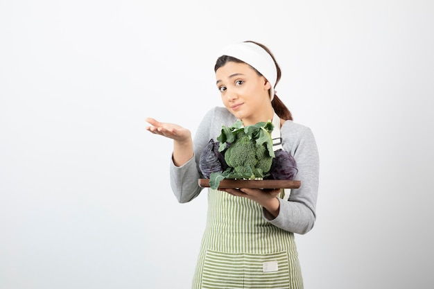 양배추와 브로콜리 접시를 들고 열린 공간을 보여주는 젊은 요리사
