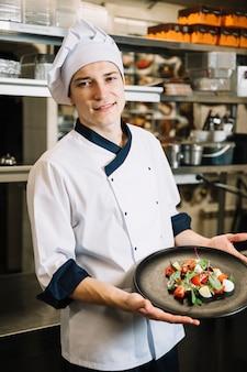 ベジタリアンサラダプレートを保持している若い料理人