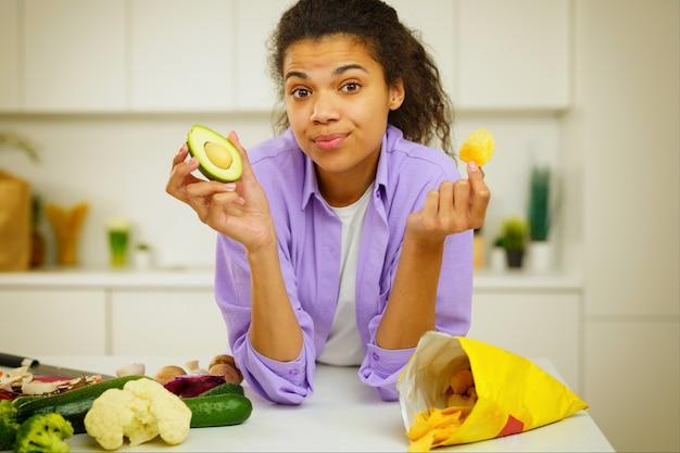 부엌의 젊은 요리사는 아보카도 또는 싸구려를 먹는 것에 혼란스러워합니다.