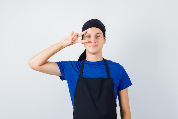 Молодой повар держит пальцы на лице в футболке, фартуке и выглядит веселым, вид спереди.