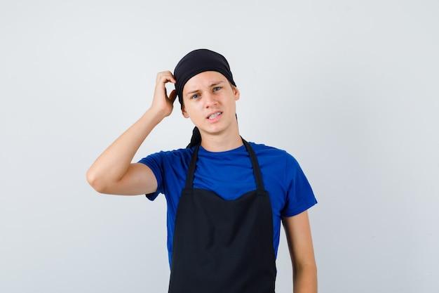 若い料理人がtシャツ、エプロンで頭を掻き、物思いにふける。正面図。