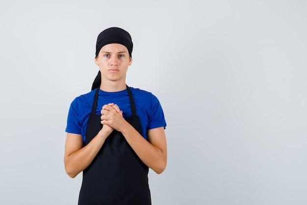 若い料理人は、tシャツ、エプロンで懇願するジェスチャーで握りしめられた手を示し、希望に満ちた正面図を探しています。