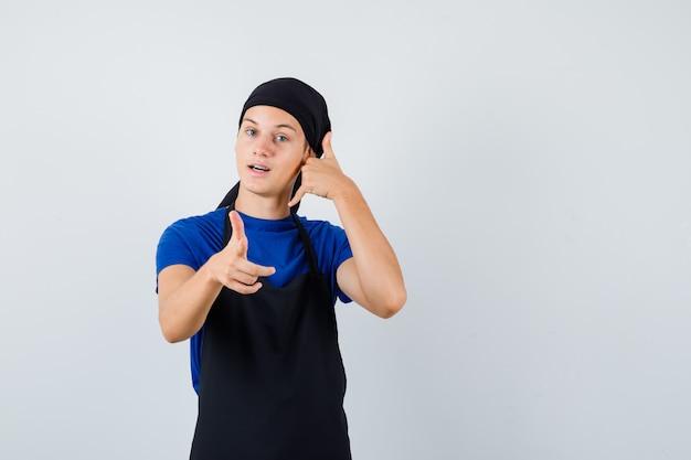젊은 요리사는 티셔츠, 앞치마를 입고 앞을 가리키며 자신감 있는 모습을 보이며 전화 제스처를 보여줍니다.