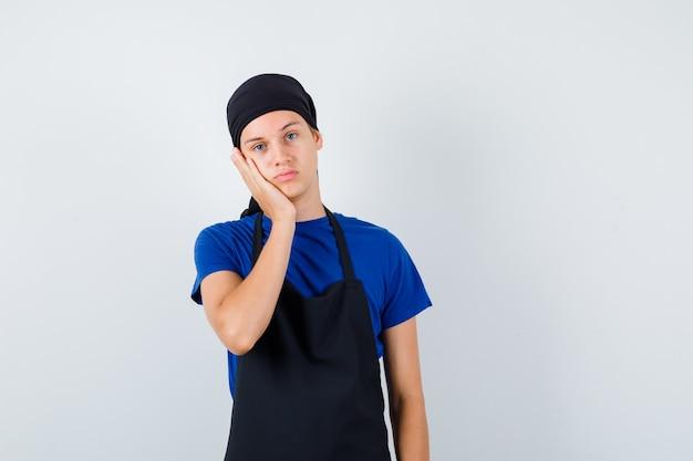 Giovane cuoco in t-shirt, grembiule appoggiato sulla guancia e guardando pensieroso, vista frontale.