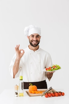 Young cook man in uniform showing ok sign and holding plate with vegetable salad isolated over white wall