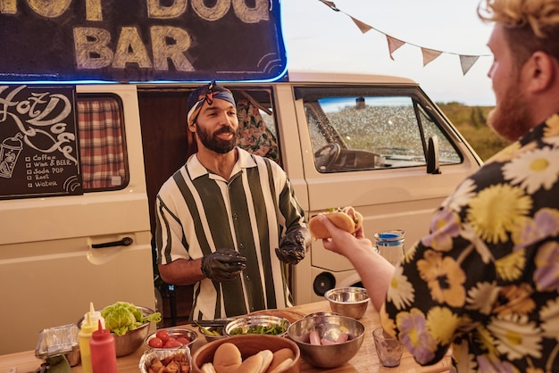 Young cook preparing hot dog for young man while they standing outdoors with van in the background