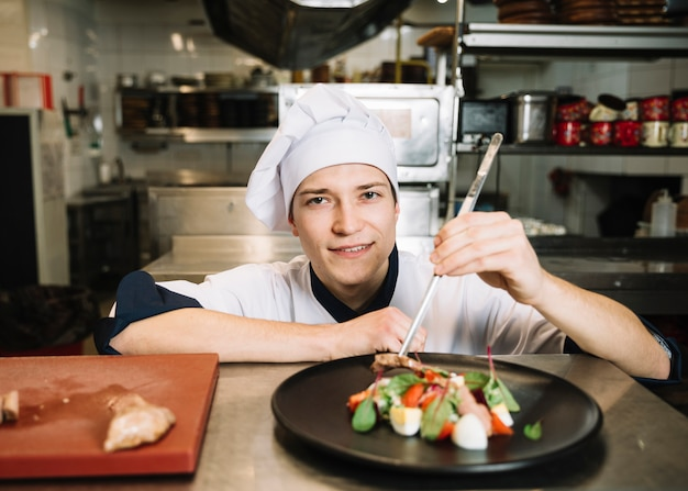 Молодой повар готовит салат с мясом за столом