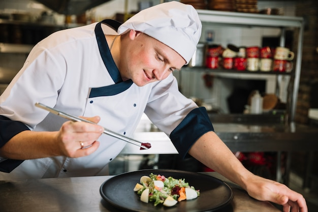 Young cook putting vegetable on plate with salad