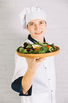 Young cook showing wooden plate with salad