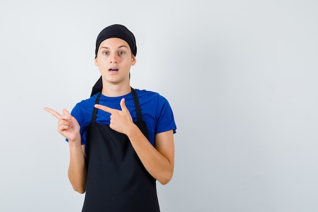 Giovane cuoco in maglietta, grembiule che punta a sinistra e sembra scioccato, vista frontale.